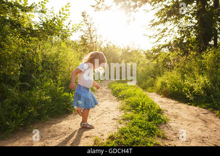 Little girl walking along a country road in the park. Summer mood. - Stock Photo