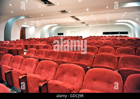 Rows of empty red seats for spectators in an auditorium, cinema or entertainment venue viewed close up - Stock Photo