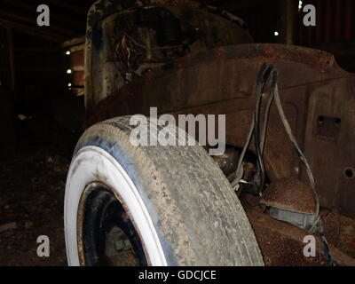 A rusty old car kept in a barn - Stock Photo