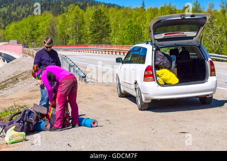 Driver helps download hitchhiker woman backpack in the white car - Stock Photo