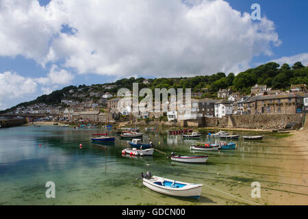 The Cornish fishing village of Mousehole with its small boats in its picturesque harbor and stone fishermen's cottages - Stock Photo