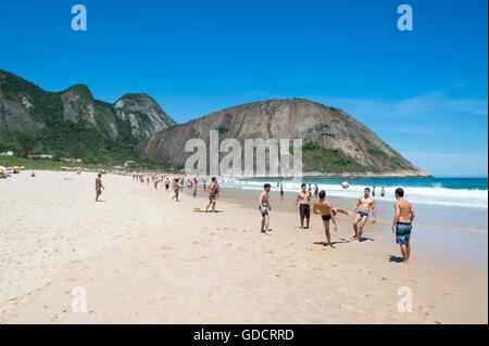 RIO DE JANEIRO - OCTOBER 31, 2015: Young carioca Brazilians play altinho beach football on the shore of Itacoatiara - Stock Photo