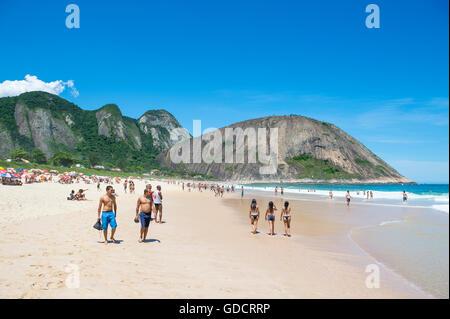 RIO DE JANEIRO - OCTOBER 31, 2015: Young Brazilians walk on the shore of Itacoatiara Beach, popular for surfing - Stock Photo