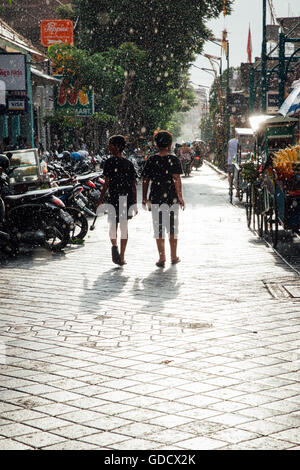 Kids walk under the sun shower on the street of Kuta, Bali, Indonesia on March 08, 2016 - Stock Photo