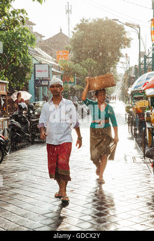 Indonesian man and woman in traditional clothes walking under the rain on the street of Kuta, Indonesia - Stock Photo