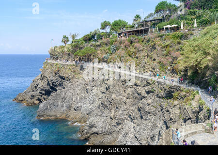 Tourists on the cliffs surrounding the Cinque Terre town of Manarola - Stock Photo