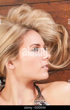 Beautiful woman laying down on the floor - Stock Photo