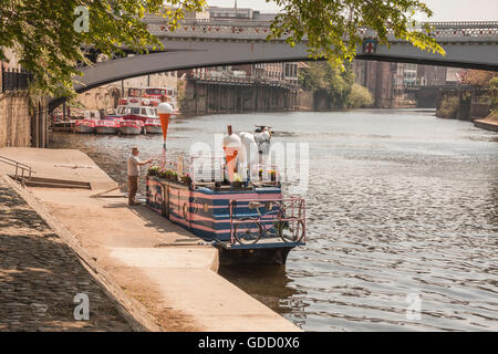 Man fixing sign on the Full Moo ice cream boat moored on the banks of the River Ouse in York with Lendal Bridge - Stock Photo