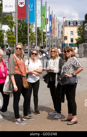 Ireland, Co Galway, Galway, Eyre Square, John Kennedy Park, American women tourists below tribe family flags - Stock Photo