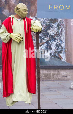 Street artist dressed as Yoda Jedi performing levitating trick outside National Gallery at Trafalgar Square, London - Stock Photo