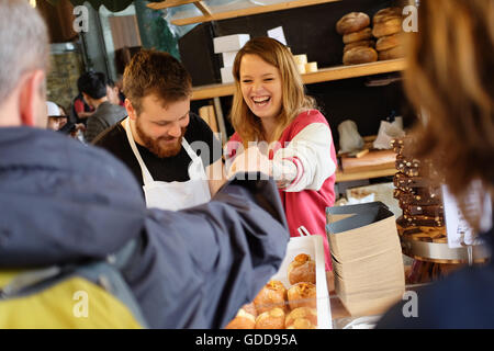A stall owner handing change back to a shopper at Borough Market in London, England. - Stock Photo