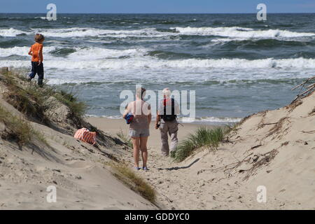 Piaski, Poland 15th, July 2016 People enjoy sunny and windy weather walking along the Baltic sea beach in village - Stock Photo