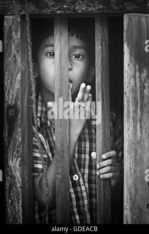Unidentified Indian boy looks through a window at home in small fishing village. Black and white - Stock Photo
