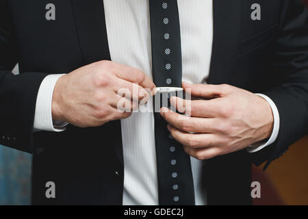 Man in black suit putting on tie clip, closeup - Stock Photo