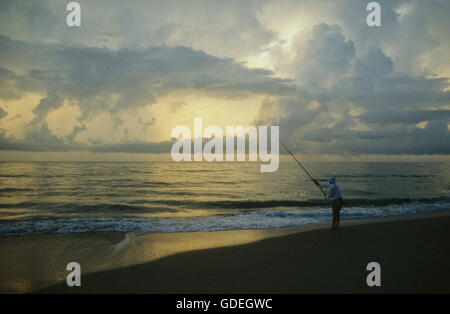 An early-morning fisherman on Florida's east coast near Daytona Beach casts into the surf while the sun rises, illuminating the scene in a golden glow. Stock Photo