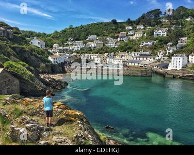 Boy standing on cliff looking at village, Polperro, Cornwall, England, UK - Stock Photo