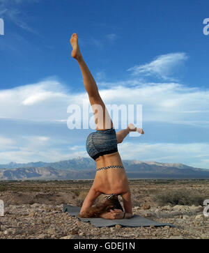 Women doing a head stand in the desert, Nevada, United States - Stock Photo