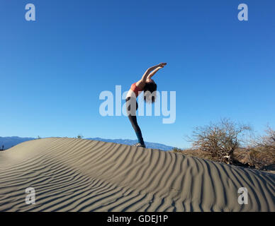 Women doing back bend on sand dune, Death Valley National Park, California, America, USA - Stock Photo