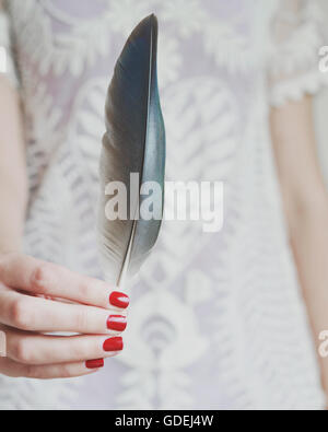 Woman holding a feather - Stock Photo