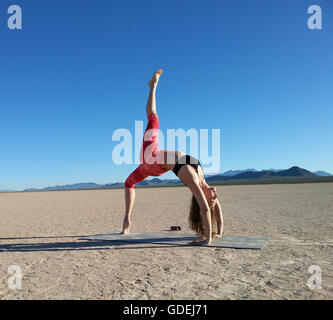 Woman doing a one legged wheel pose in a dry lake, Nevada, America, USA - Stock Photo