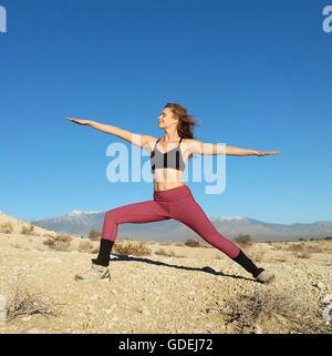 Woman doing a warrior pose, Nevada, America, USA - Stock Photo