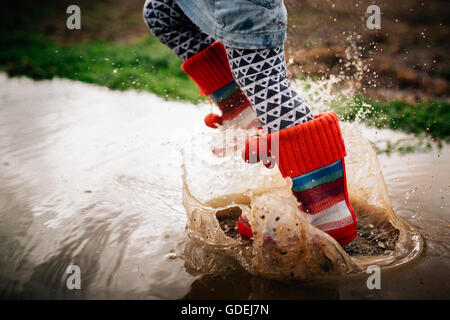 Girl Jumping in muddy puddle - Stock Photo