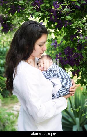 Mother holding sleeping baby in garden - Stock Photo