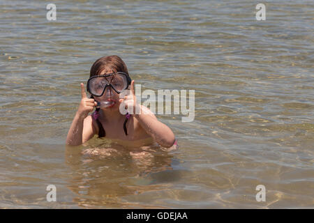 Girl wearing snorkeling mask in the sea showing size of fish with her hands - Stock Photo