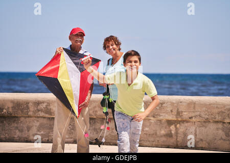 Happy tourist family on holidays in Cuba. Hispanic grandpa, grandma and grandson having fun flying a kite - Stock Photo