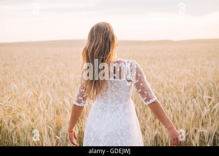 Woman walking through wheat field - Stock Photo