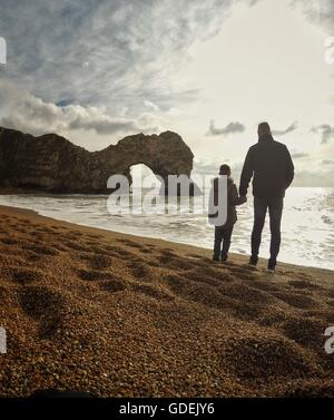 Father and son holding hands on beach, Durdle Door, Dorset, England, UK - Stock Photo