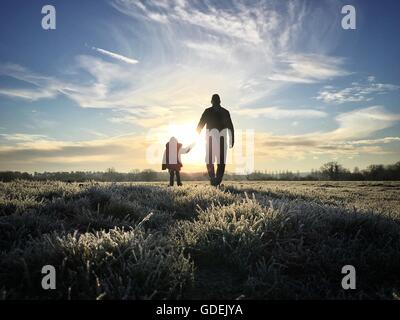 Silhouette of father holding daughter's hand - Stock Photo