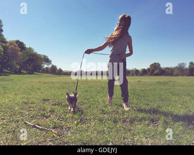Girl walking small dog in park - Stock Photo