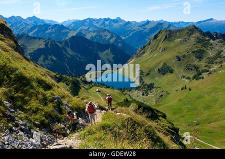 Hikers at Lake Seealpsee, Nebelhorn, Oberstdorf, Allgaeu, Bavaria, Germany - Stock Photo