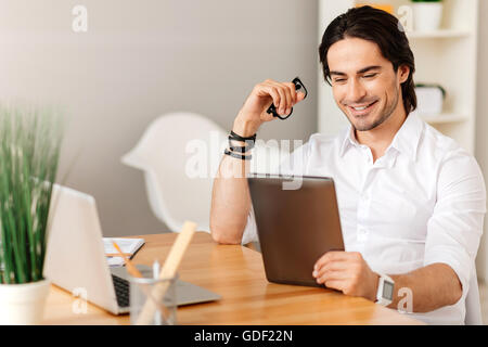 Pleasant positive man sitting at the table - Stock Photo