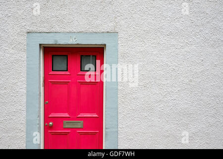 A red front door to a traditional terraced house in Scotland. - Stock Photo