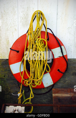Old weathered life preserver, life buoy or life ring and rope on a ...