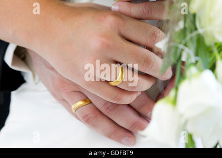 Hands of a bride and groom, wedding rings, bridal bouquet - Stock Photo