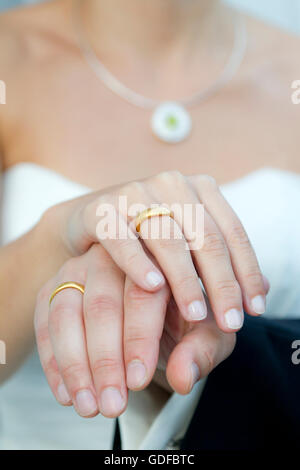Hands of a bride and groom, wedding rings - Stock Photo