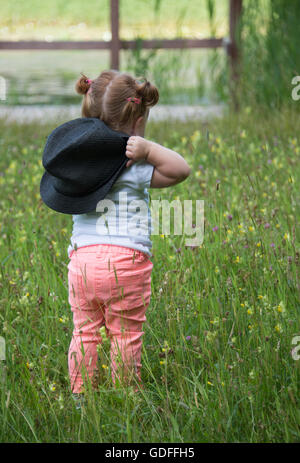 AMSTERDAM,NETHERLANDS- JULI 9, 2016: Unidentified little girl 18 month old with red hair wlaking in green grass - Stock Photo