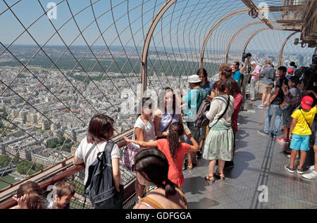 Tourists posing for photos on the upper level walkway of the Eiffel Tower in Paris, France. - Stock Photo