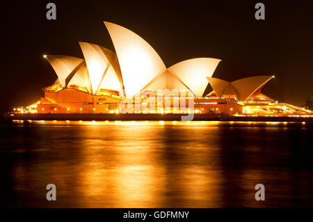 Illuminated Sydney Opera House reflects in the water of the harbour. - Stock Photo