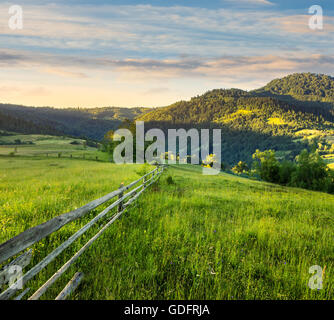 composite rural landscape. fence on the meadow near trees on the hillside. conifer forest on the mountain top in - Stock Photo