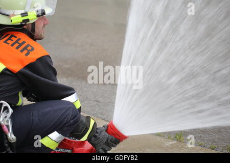 A Firefighter with monitor water cannon spray lance - Stock Photo