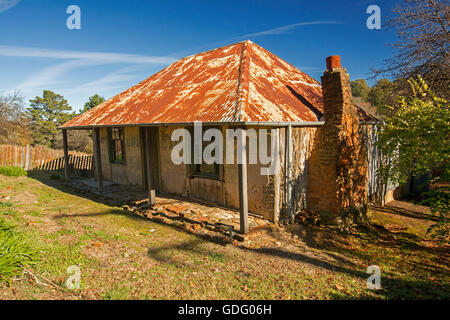 Historic building, old  miner's cottage with rusty roof, red brick chimney, flaking paint, against blue sky at Hill - Stock Photo