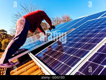 Workman installing solar panels on house roof - Stock Photo