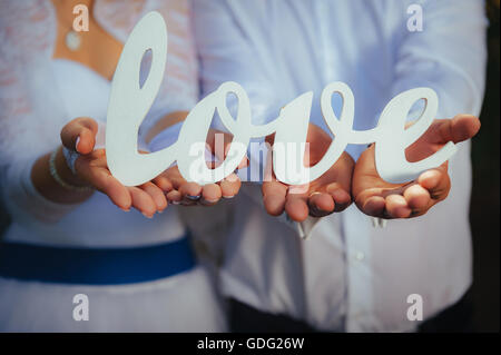 Closeup shot of bride and groom hands holding the word Love. - Stock Photo
