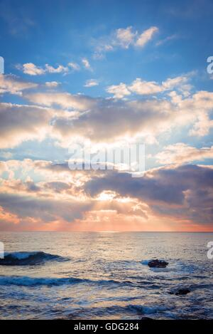 Beautiful sunrise over the sea. Sun beams break through the clouds. - Stock Photo