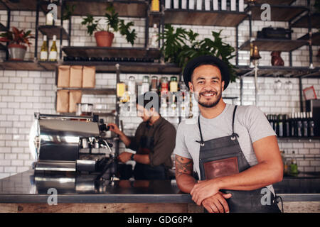 Portrait of male coffee shop owner standing at the counter with barista working in background making drinks. - Stock Photo