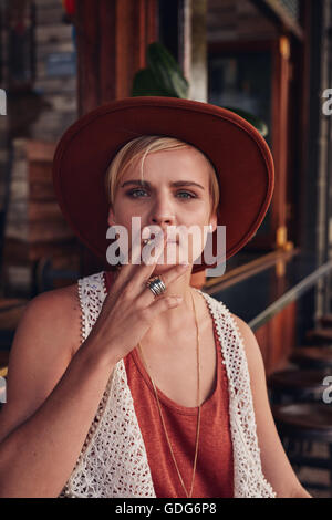 Portrait of young woman with hat smoking a cigarette in a coffee shop. Stock Photo